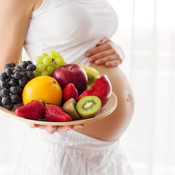 Pregnant woman holding fruit plate
